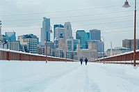Rear view of two people jogging on a snow covered road, Minneapolis, Minnesota, USA