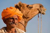 Close_up of a man with a camel in the background, Thar Desert, Khuri, Sikar, Rajasthan, India