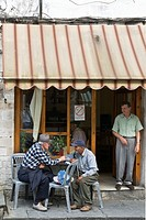 Old men talking outside a cafe in the centre of the bazaar area of Gjirokastra in southern Albania