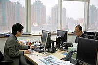 Two businessmen working in an office, Shanghai, China