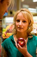 Portrait of a young woman holding an apple in a supermarket