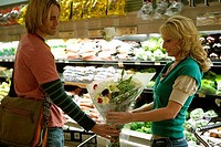 Young man giving a bouquet of flowers to a young woman in a supermarket