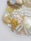 Group of gold, pink, silver and translucent beads and shells on glass plate