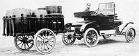 Rear view of a milkman driving a car attached with a vehicle trailer