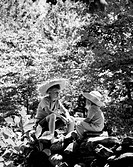 Two boys seated on rocks talking in woods