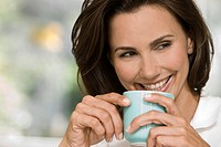 Smiling woman holding cup of coffee