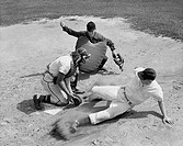 High angle view of a baseball player sliding on home base and a catcher trying to tag him