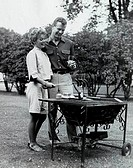 Young couple cooking sausages on a barbecue grill