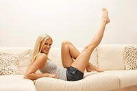 Blond young woman lifting her legs on couch