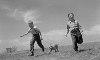 Pair of children running in field with dog