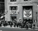 High angle view of large group of people waiting in line in front of a bank building