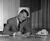 Businessman writing at desk