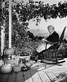 Senior woman sitting in a rocking chair and peeling an apple