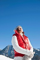Woman standing with eyes closed in winter landscape, Tannheimer Tal, Tyrol, Austria