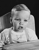 Close_up of a baby sitting in a high chair