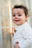 Portrait of smiling one year old boy with large dark eyes and a blurry, distorted background caused by using a ´lensbaby´ lens