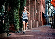 Female athlete running on sidewalk, Midtown, San Diego, California, USA