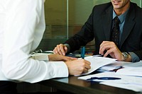 Person signing document in meeting with executive
