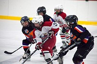 Hockey players age 10 bringing puck down ice  St Paul Minnesota USA