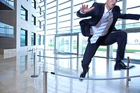 Businessman jumping over ropes in lobby (thumbnail)