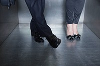Man and woman standing in elevator, man moving foot toward woman´s foot