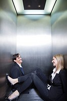 Professionals trapped in elevator, sitting on floor chatting