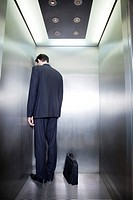 Businessman standing in corner of elevator with back to camera and head down