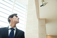 Businessman looking up at security camera