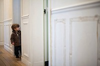 Toddler boy standing in hall, peeking in doorway