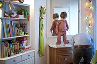 Toddler boy standing on top of changing table in nursery