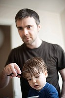 Father cutting toddler son's hair