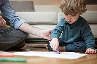 Toddler boy sitting on floor with father, drawing on paper (thumbnail)