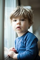 Toddler boy by window, portrait (thumbnail)