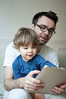 Father and young son looking at digital tablet together