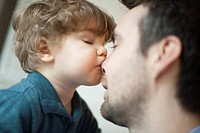 Toddler boy kissing father's nose