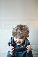 Toddler boy playing with headphones, portrait