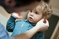 Father helping toddler son use earphones