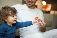 Toddler boy reaching for cookie in father's hand