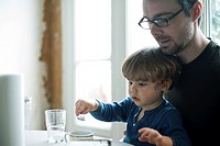 Toddler boy learning to use spoon, father watching affectionately