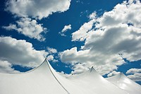 White Tent Top Against a Cloudy Sky
