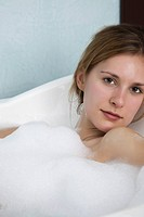 Woman relaxing in bubble bath, portrait