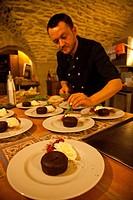 A chef prepares dessert.