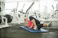Woman exercising on mat in gym