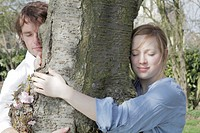 Couple hugging tree in park