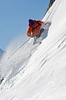Skier turning on steep mountain face