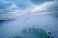 A ships bow ploughs through huge waves rounding treacherous Cape Horn.
