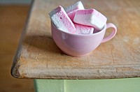 Pink marshmallows in pink cup on breakfast table