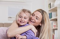 Germany, Bavaria, Munich, Mother embracing daughter, smiling