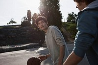 Germany, Berlin, Teenage boys playing basketball in playground