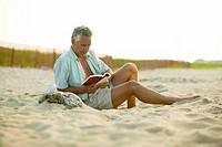 Man reading book at Charlestown Beach, Rhode Island.